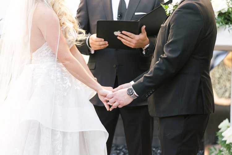 Bride and Groom Holding Hands in Front of Officiant